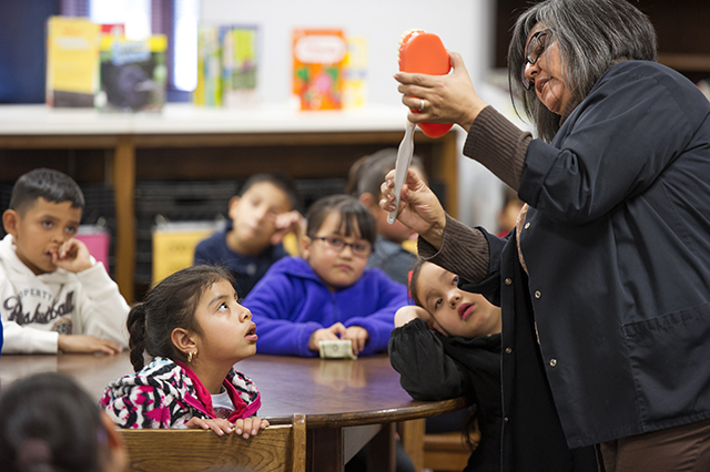 Janie Villarreal demonstrates brushing techniques to elmentary school students.