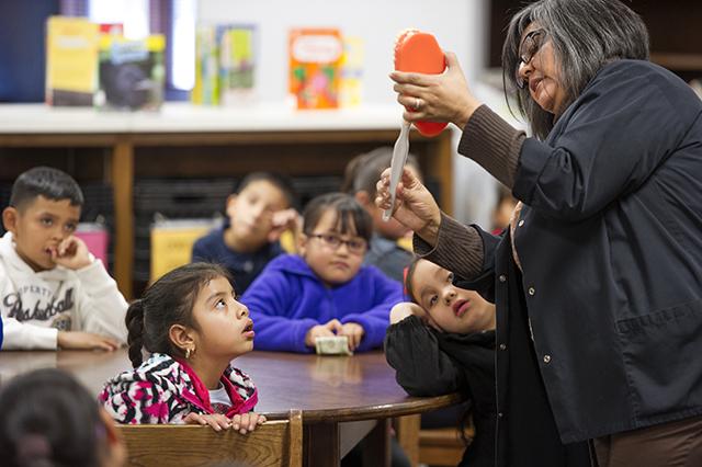 Janie Villarreal demonstrates brushing techniques to elmentary school students.