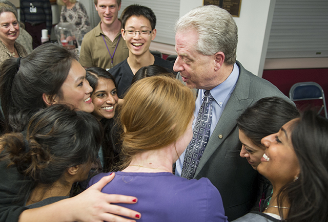 Students surprise Dr. Robert Spears with a group hug during a Dec. 9 farewell reception at the dental school.