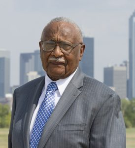Dr. Claude Williams stands in front of the Dallas skyline.