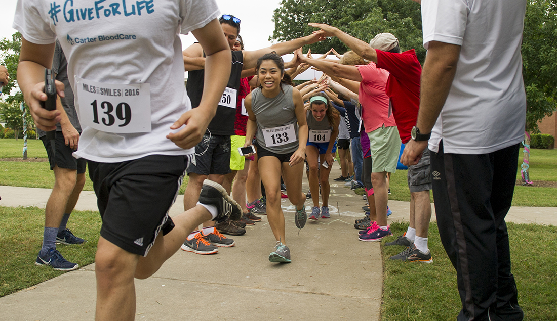 Runners run through a tunnel created by people interlocking their hands.