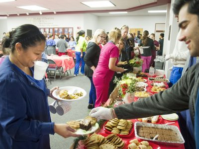 A Texas A&M College of Dentistry student serves a staff member dessert during the annual GRACE lunch event.