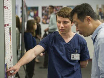 Pekar discusses his poster with Dr. Xiaofang Wang during the College of Dentistry's April 5 Research Scholars Day.