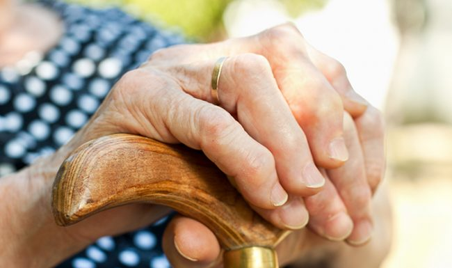 close-up of elderly woman's hands holding a cane